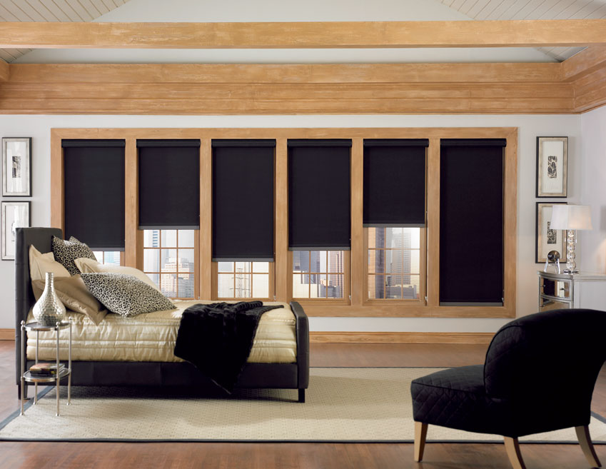 A bedroom wall of windows with black Genesis® Custom Roller Shades