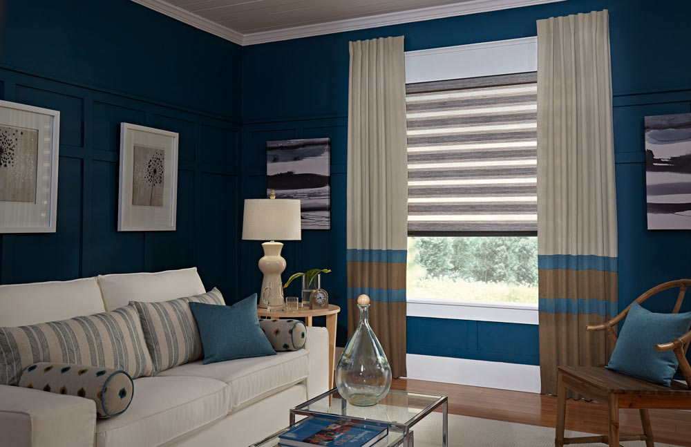 brown Allure® Transitional Shade against a dark blue wall with tan, brown, and blue striped Interior Masterpieces® Draperies behind a couch with matching custom Pillows