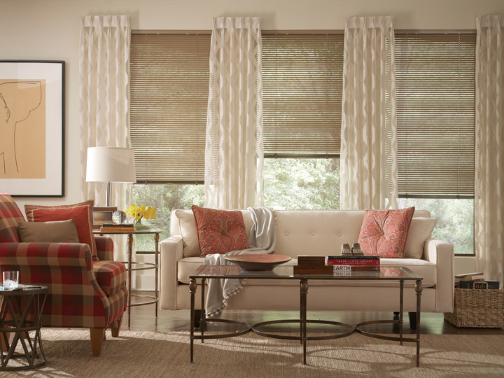 Light brown Classic Collection® Aluminum Blinds & Interior Masterpeices® cream colored Draperies and light red floral Custom Pillows on a light colored couch