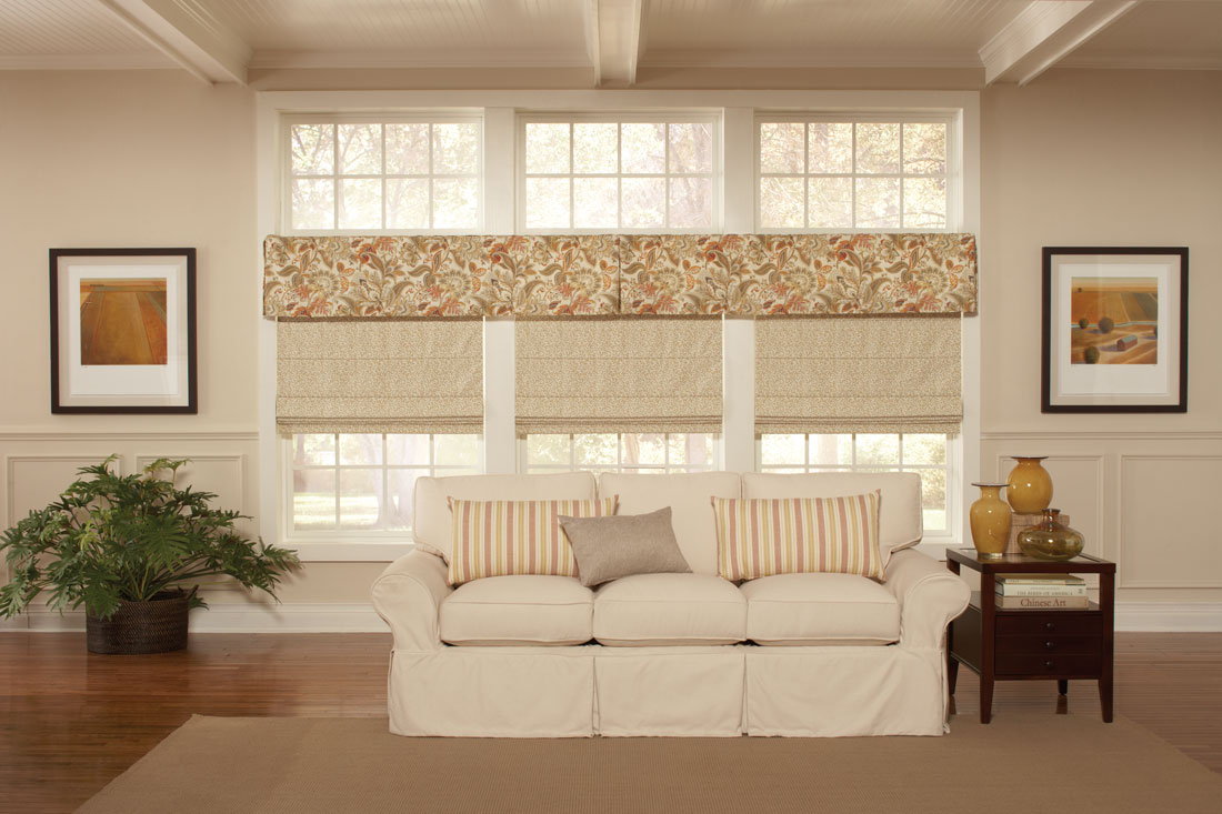 three cream colored Interior Masterpieces® fabric shades with a floral patterened cornice spanning the width of all three above behind a white couch tha thas custom accent pillows