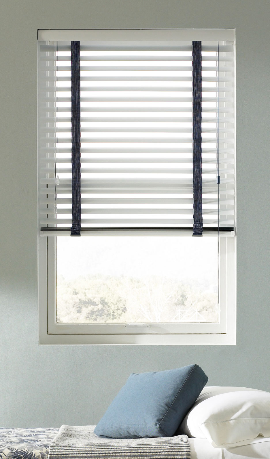 White Classic Collection® Aluminum Blinds with blue ladders against a light blue wall in a bedroom