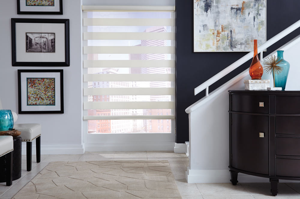 white Allure® Transitional Shade at the bottom of a stairway with a blue wall and painting on one side and a white wall and picture frames on the other