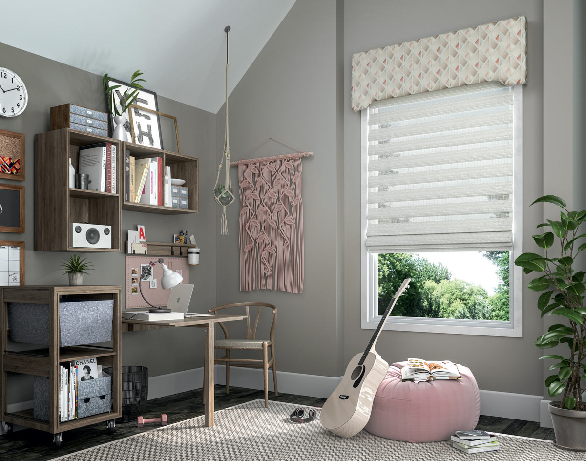 White Manh Truc® Woven Wood Shade with pink white and gray Interior Masterpieces® Fabric Cornice with a geometric pattern against gray walls and behind a pink bean bag chair and guitar