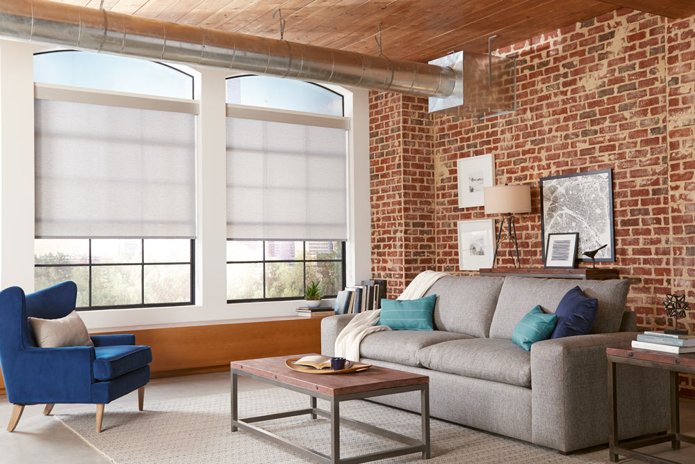 two tan Genesis® Roller Shades against brick walls with a gray couch that has blue and teal Interior Masterpieces® Custom Pillows