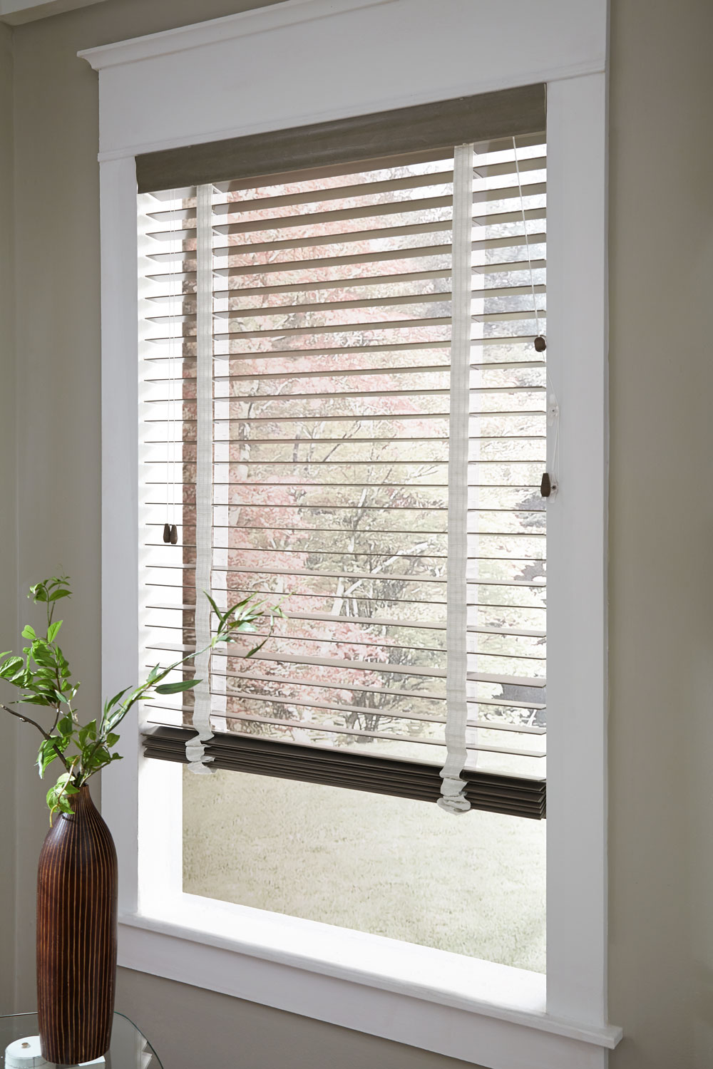 closeup of brown Heartland Woods® Wood Blinds with Decorative Tape with a green plant in front