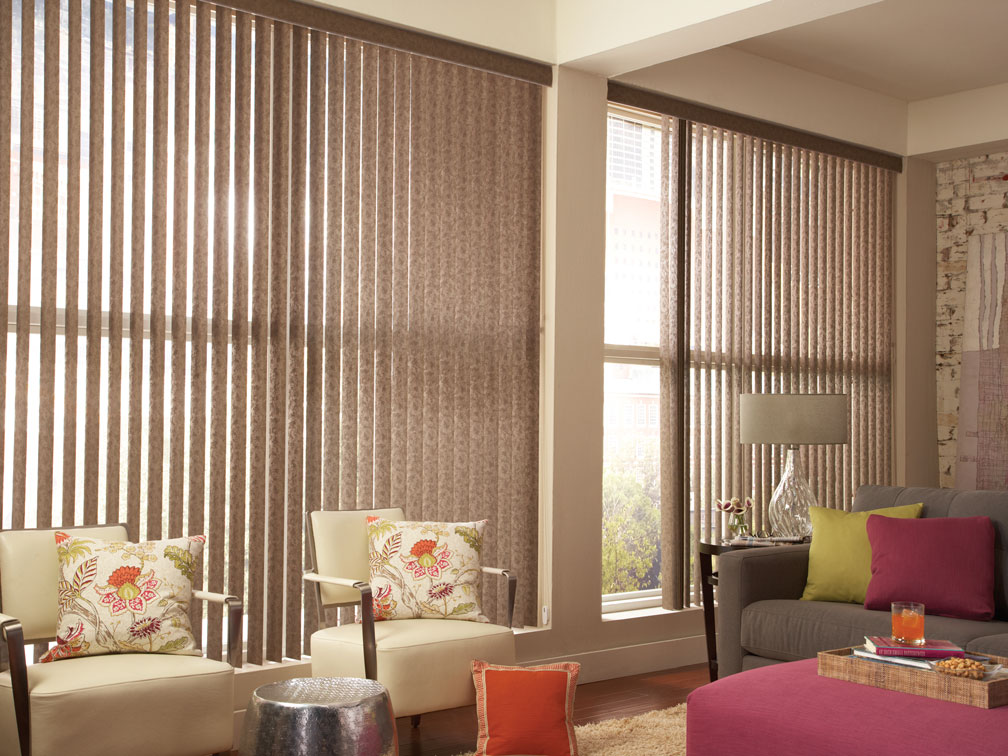 2 large brown Discoveries® Vertical Blinds with chairs and a sofa sitting in front that have Sheer Visions® material custom pillows