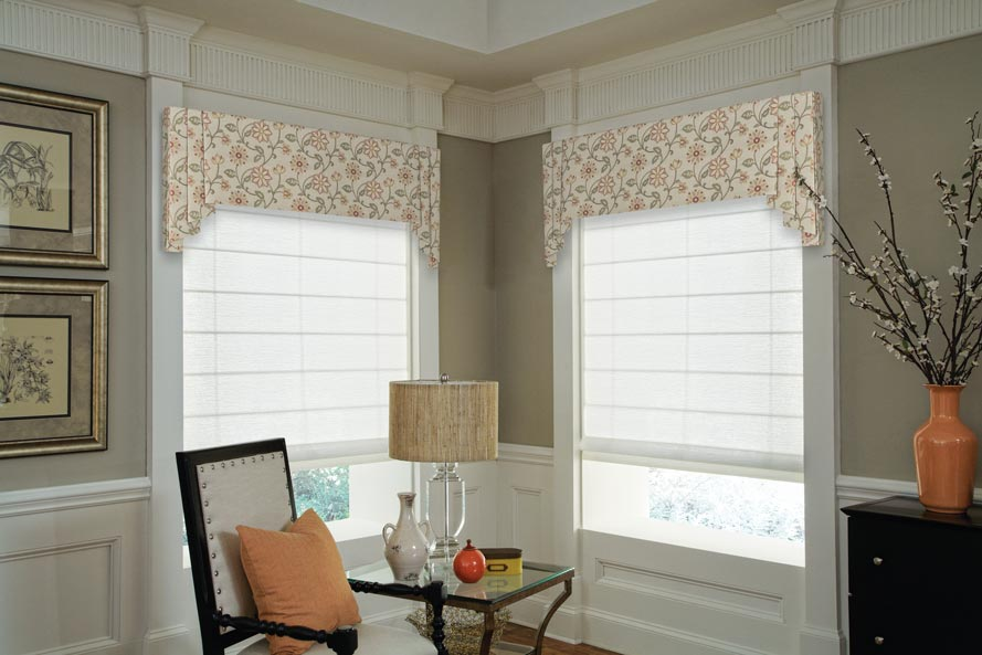 Two white Genesis® Roman Shades with tan floral patterened Interior Masterpieces Valances and a chair that has a peach colored Custom Pillow