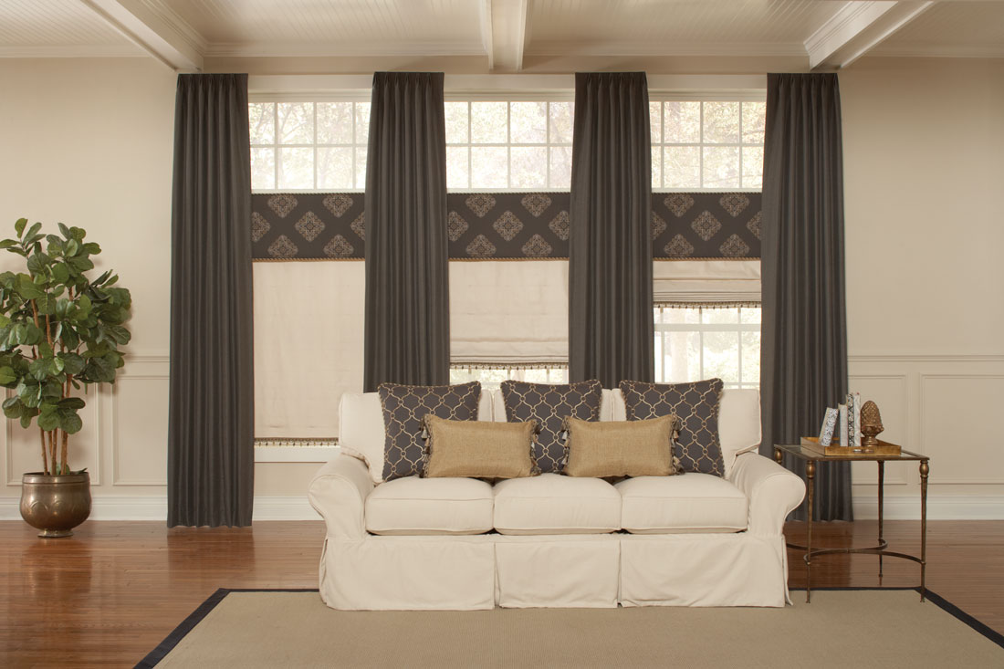 three tan Interior Masterpieces® fabric shades with Embellishment trim tassles and dark brown fabric wrapped cornices above with long flowing dark brown draperies between each behind a white couch with custom accent pillows