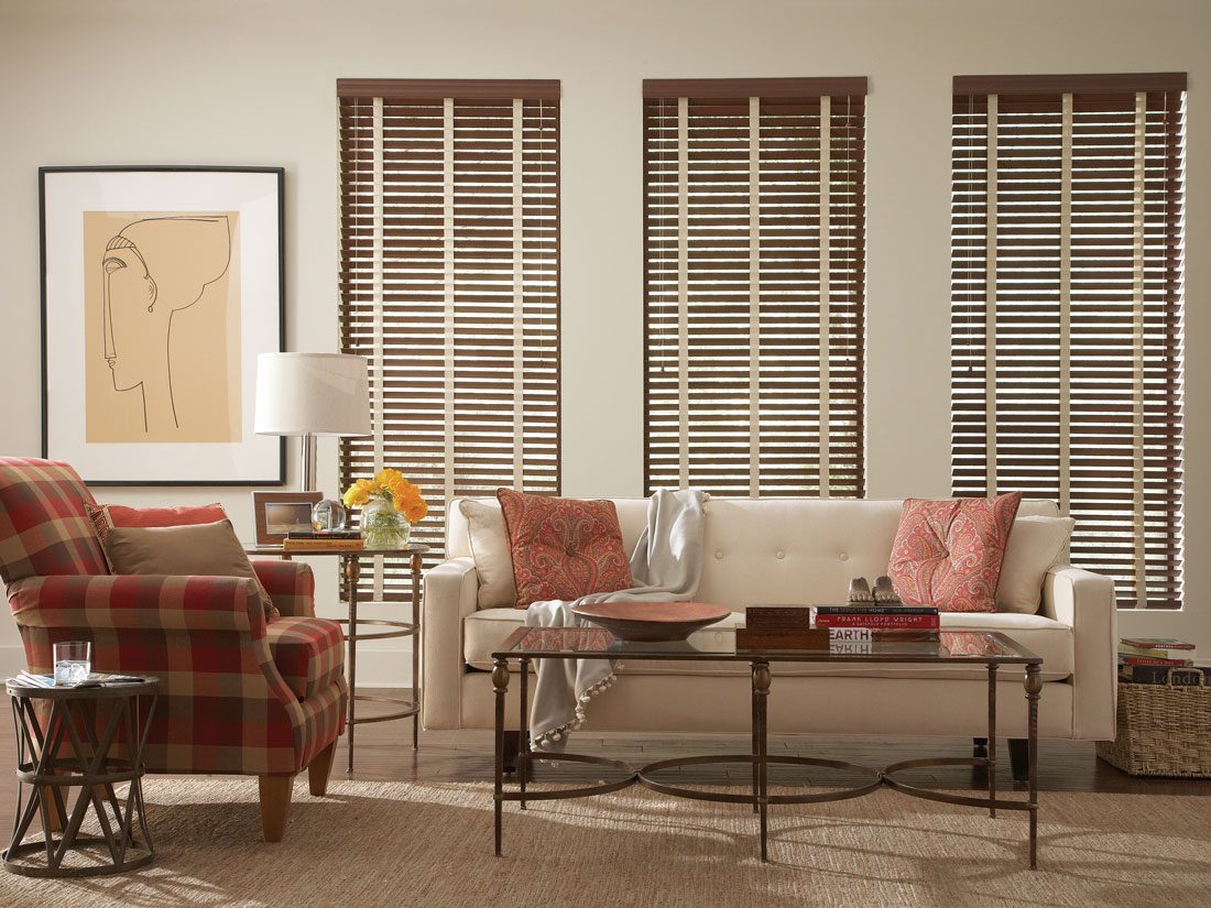three dark brown Fidelis® Faux Wood Blinds with light colored Banding in an room with a white couch and red plaid chair with Interior Masterpieces® pillows on them