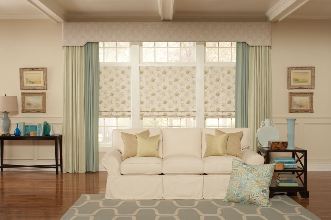 three tan floral patterned Interior Masterpieces® fabric shades with a large fabric wrapped cornice spanning the windows with light and dark green draperies hanging at each end behind a white couch with custom pillows
