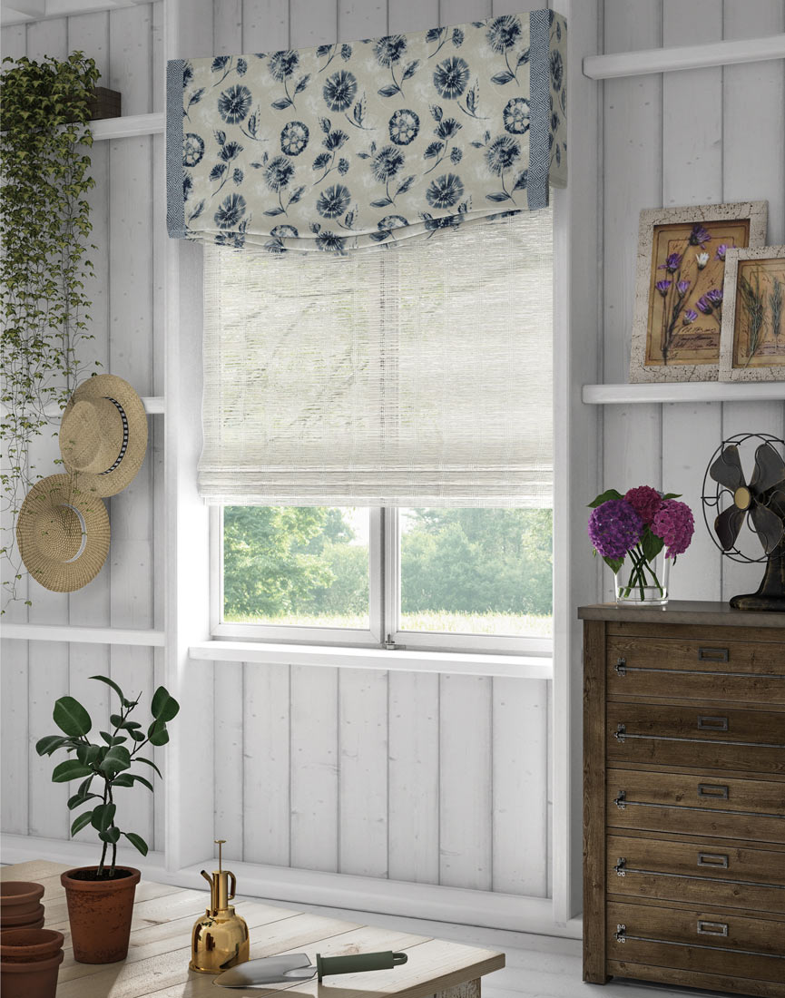 a white Manh Truc® Woven Wood Shade with a light white and blue floral patterned Interior Masterpieces® Fabric Valance with light blue Decorative Banding in a shed with gardening tools around