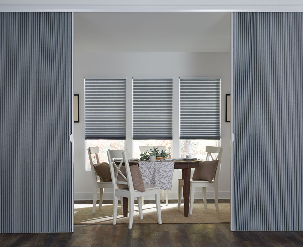 three blue Parasol® Cellular Shades with a large blue Glissade Panel System acting as a room divider for a dining area with a brown table that has Interior Masterpieces accessories on it surrounded by brown chairs