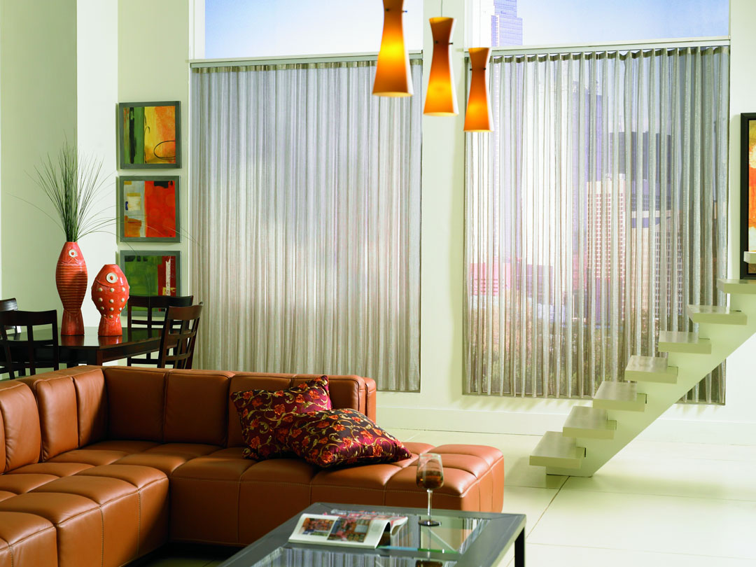 Two large picture windows with Sheer Visions® Vertical Blinds hanging in them with a red couch and stairway in front of them and paintings on the wall beside