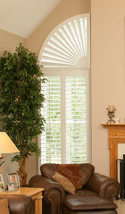 off white Parke® Shutters with a Quarter Circle Custom Shape and a tall potted plant in the foreground and a brown chair