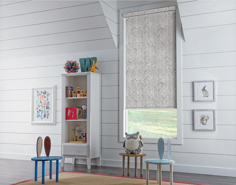 white Genesis® Cassette Roller Shade with a gray and green chevron pattern in a child's room with tiny chairs and a stuffed owl