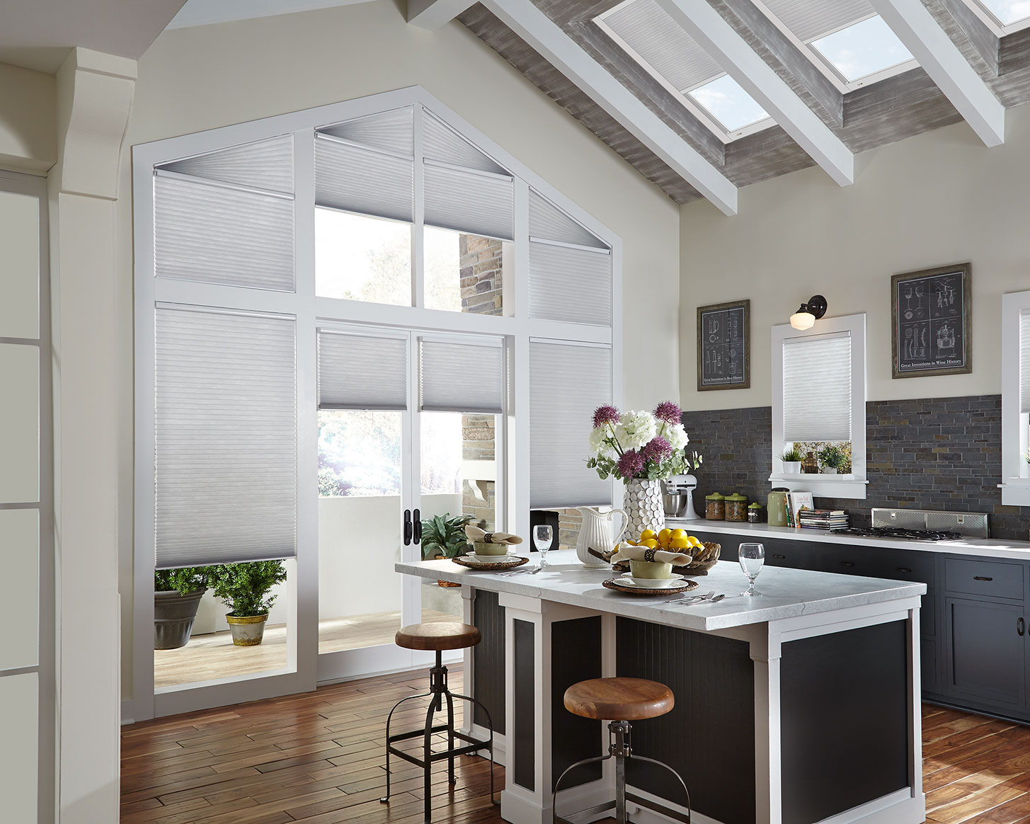 Off-white cellular shades treat an arched wall of windows and skylights in an open space kitchen area with a large island and wood floors.