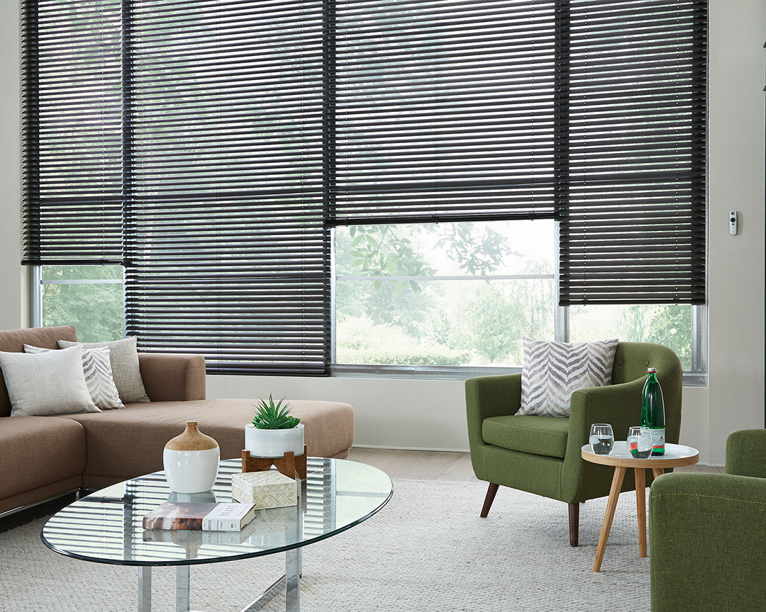 Dark Classic Collection® Motorized Aluminum Blinds in a room with a brown couch, green chair and Interior Masterpieces® pillows