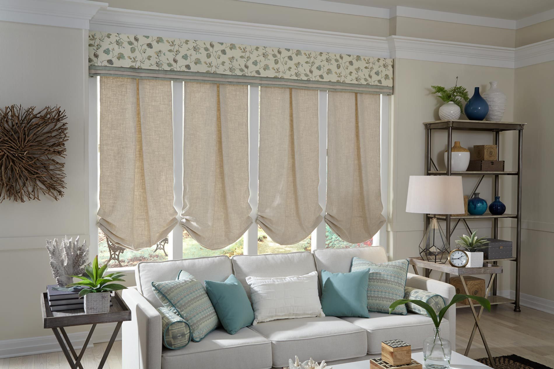 4 light tan Interior Masterpieces® fabric shades with a custom cornice spanning the width of all four and a light gray couch that has custom accent pillows