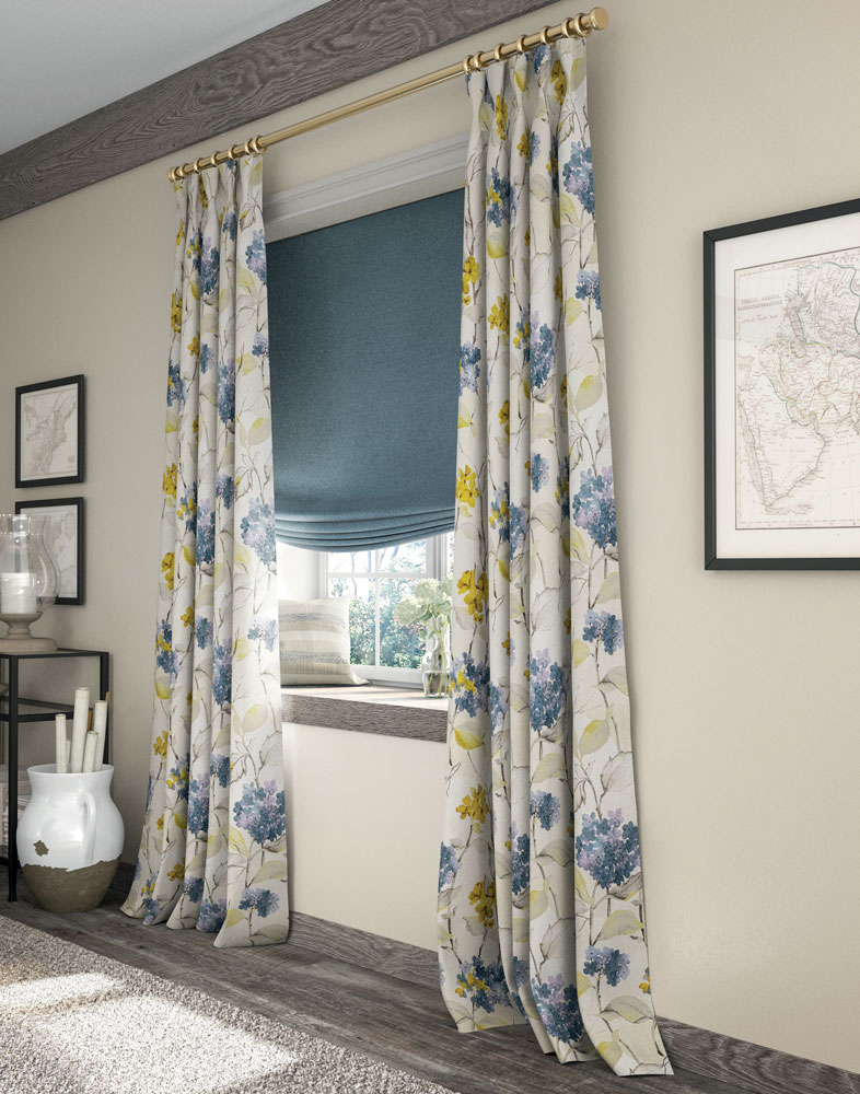 blue Interior Masterpieces® fabric shade with white, blue, and yellow floral pattern draperies hanging in a window with a custom pillow and flowers