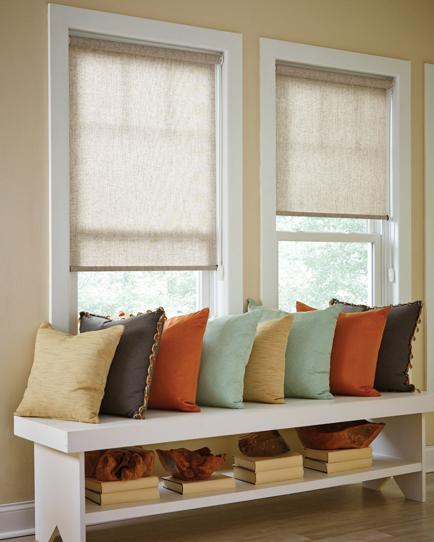 two light beige Genesis® Roller Shades with a bench that has several brightly colored Interior Masterpieces® Custom Pillows