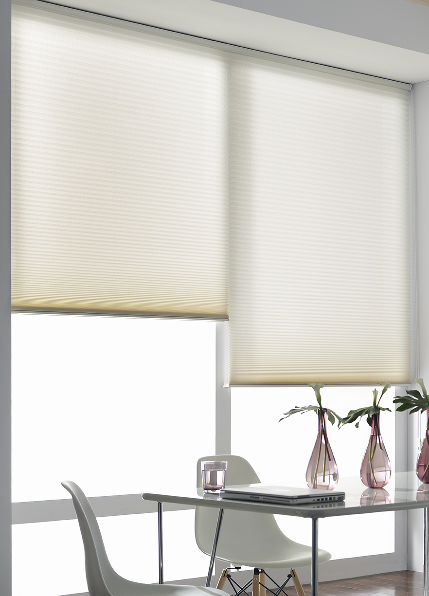 Two cream cellular shades hang on one headrail in a large window of a bright, light modern dining and work space area.
