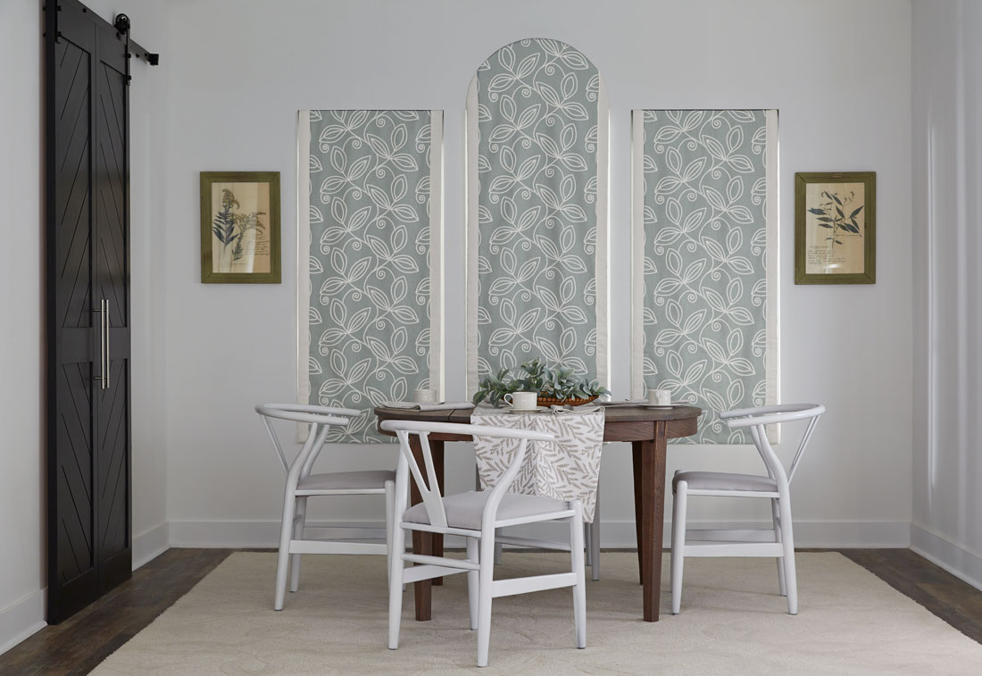 Three light blue floral patterned Interior Masterpieces® fabric shades with a custom arch top in the middle behind a brown table with white chairs