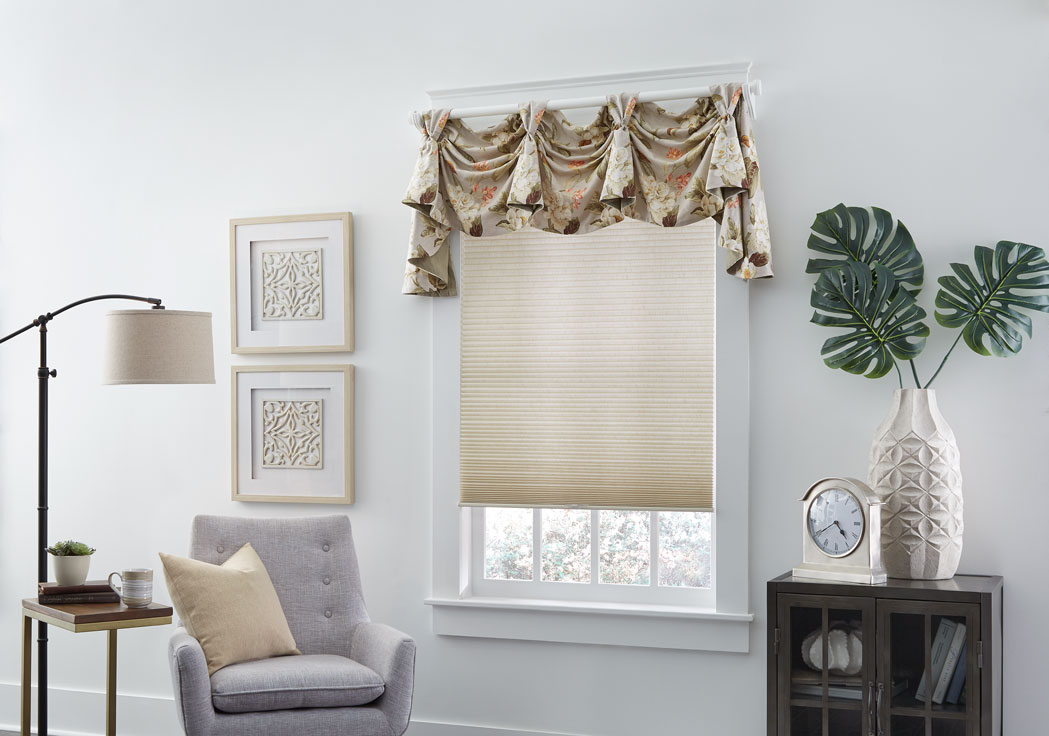 Parasol® Cellular shade in a tan material with a custom Interior Masterpieces® valance in a floral tan materian with custom Decorative Hardware