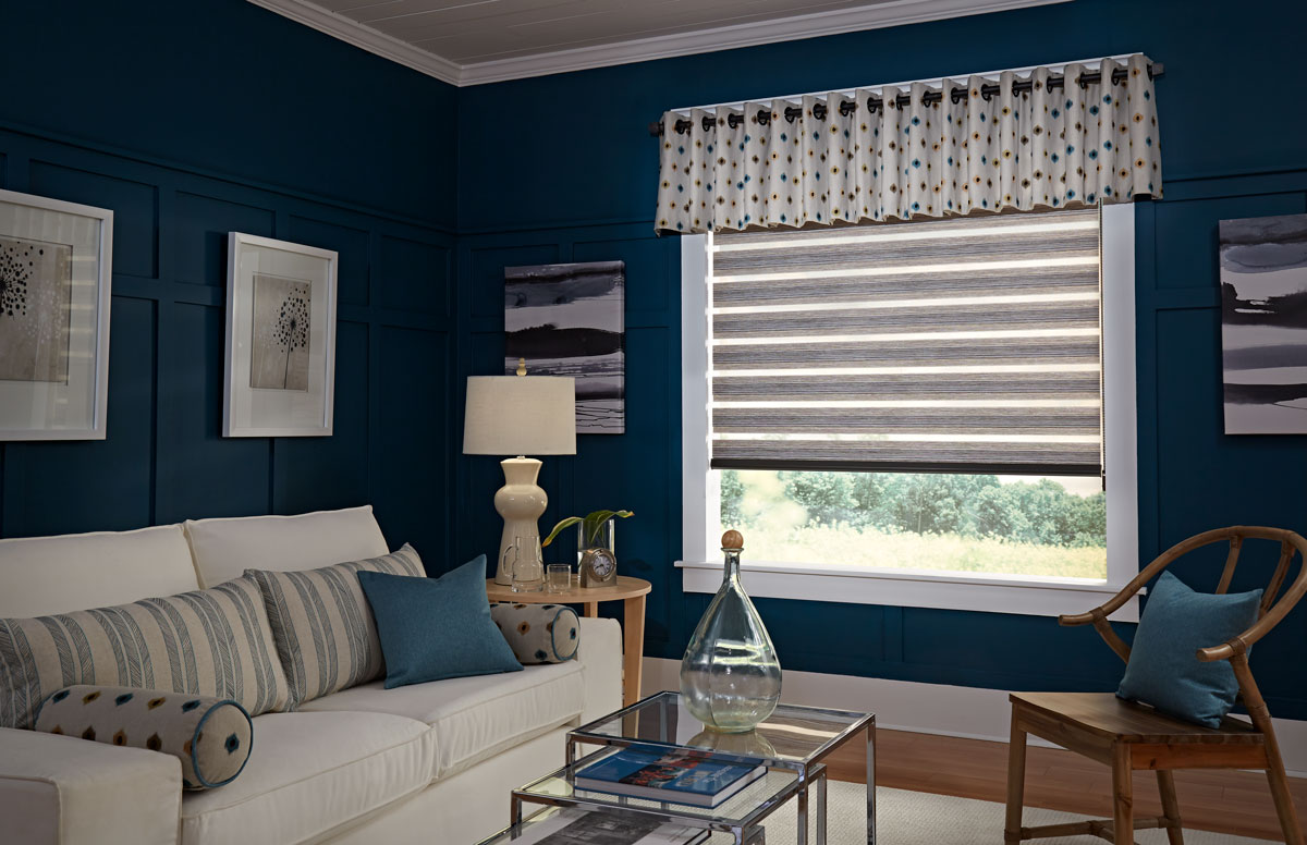 light brown Allure® transitional shade with custom Interior Masterpieces® valance hanging on a black custom rod with grommets and finials in a blue room with a cream colored couch that has accent pillows on it