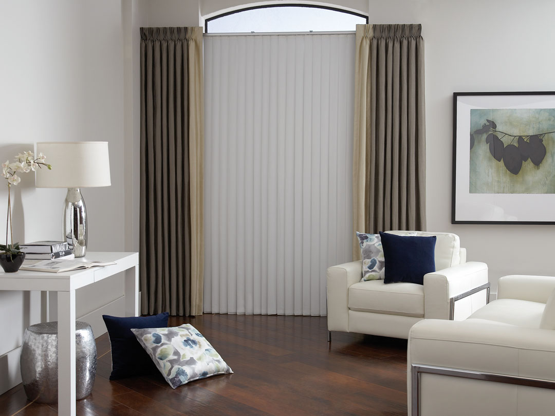 White Sheer Vision® Vertical Blinds with brown and tan custom draperies and pillows from our Interior Masterpieces® collection in a room with white chairs and a table