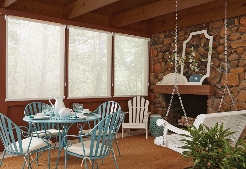 three large Genesis® Custom Roller Shades in a cabin with blue and white furniture in the foreground