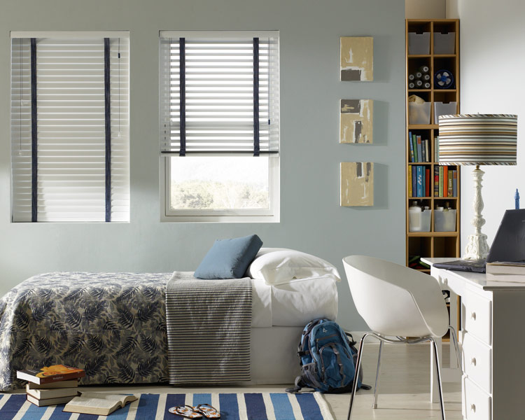 white Classic Collection® Aluminum Blinds with blue Decorative Tape behind a bed with Interior Masterpieces® bedding in blue and grays