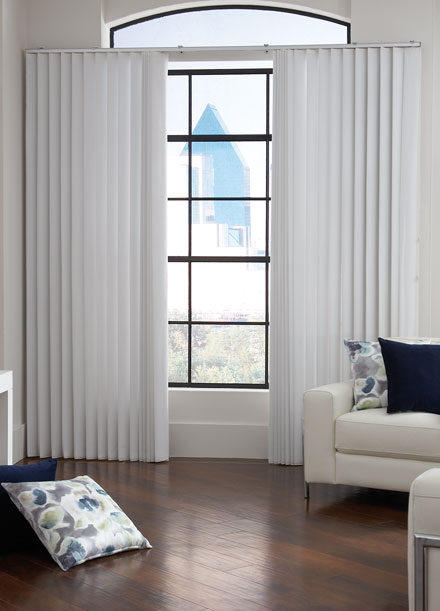 White sheer fabric wrapped vertical blinds hang in a window of a room with dark wood floors, modern white leather chairs with metal accents and custom throw pillows in navy and floral.
