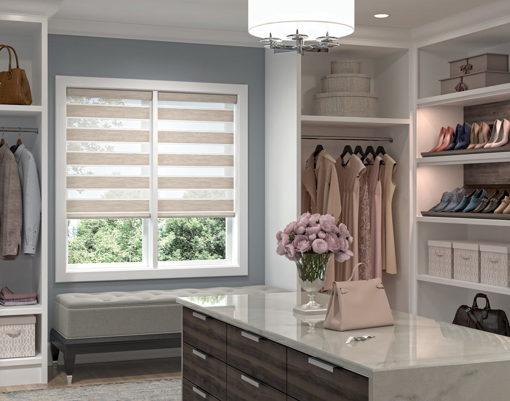 two light brown Allure® Transitional Shades in a closet with clothes hanging nearby and a dresser with flowers in the foreground