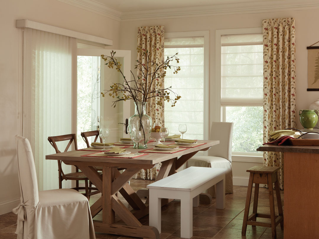 white Discoveries® Vertical Blinds on one large patio door with custom Genesis® shades with Interior Masterpieces® draperies on the other wall in a kitchen with a brown table and white covered chairs