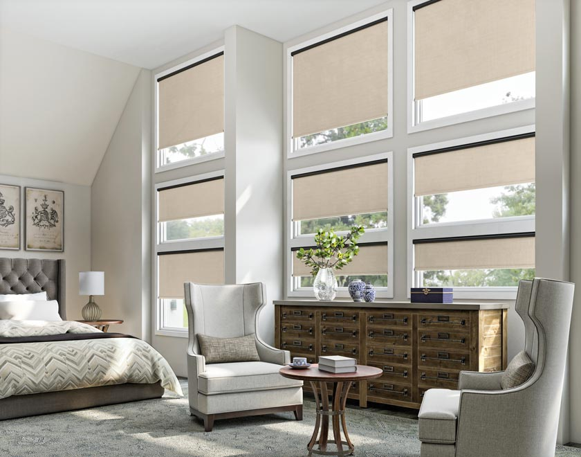 Several tan colored Genesis® Motorized Roller Shades in a bedroom with a bed and a brown dresser in front of them