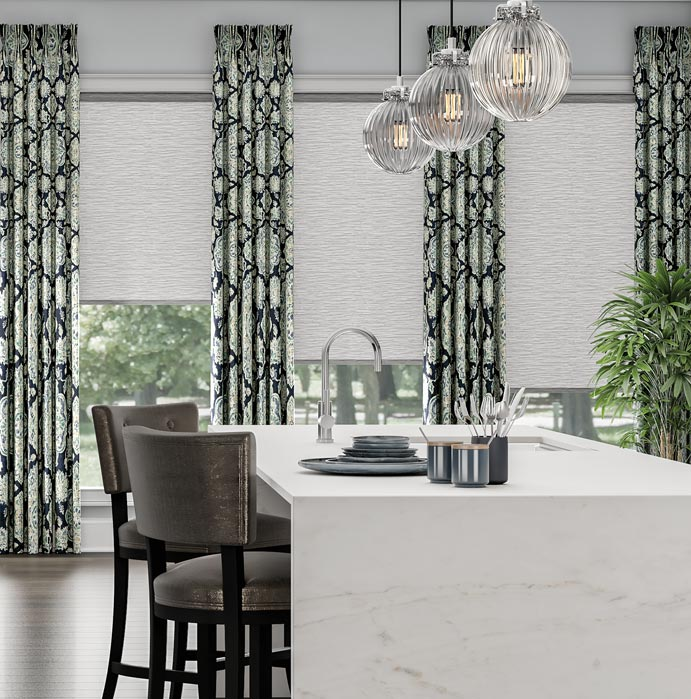 Three white Genesis® Roller Shades with drapery panels from Interior Masterpieces® in a kitchen setting
