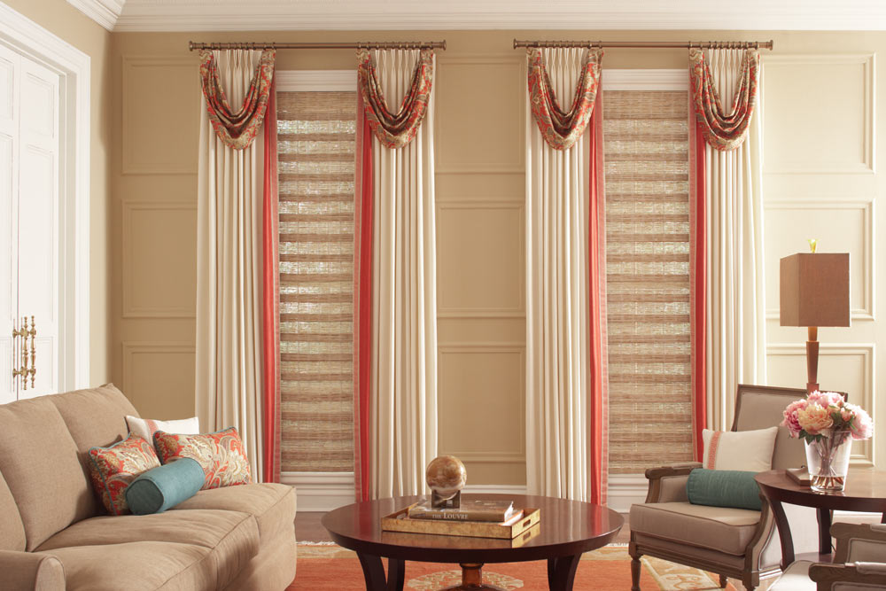 Two long light brown Manh Truc® Woven Wood Shades with tan and red Interior Masterpieces® Draperies on bronze Custom Hardware