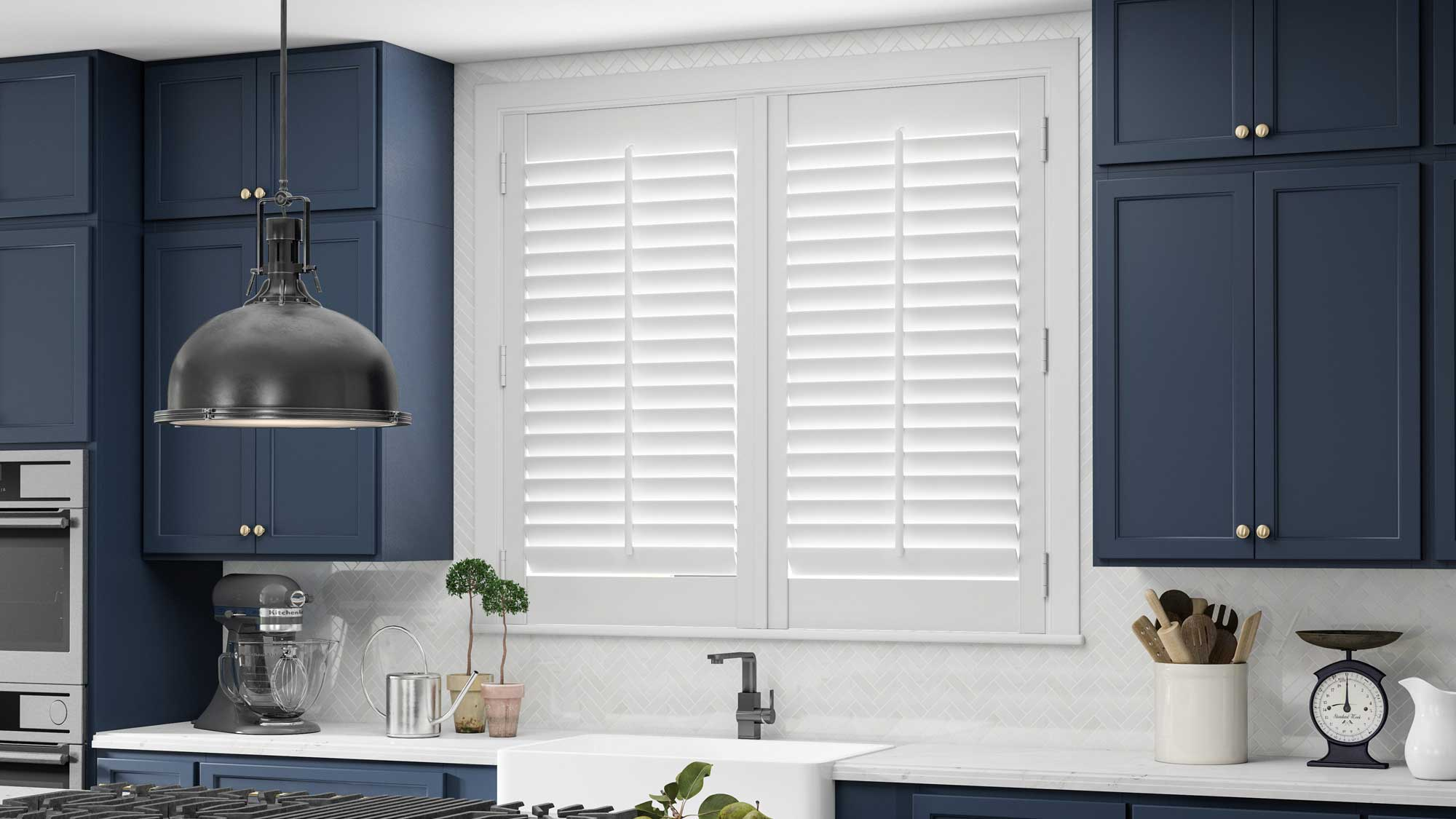 white Parke® Shutters in a kitchen with blue cabinets, a sink, and an island stove top with marble counters in the foreground