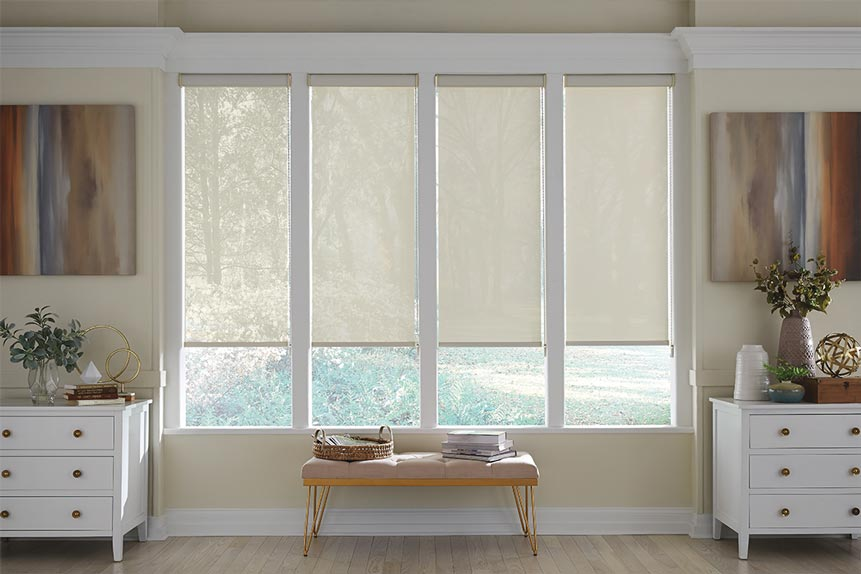 Four light cream colored Genesis® Cassette Roller Shades showing varying opacities with the lightest on the left and the darkest on the right