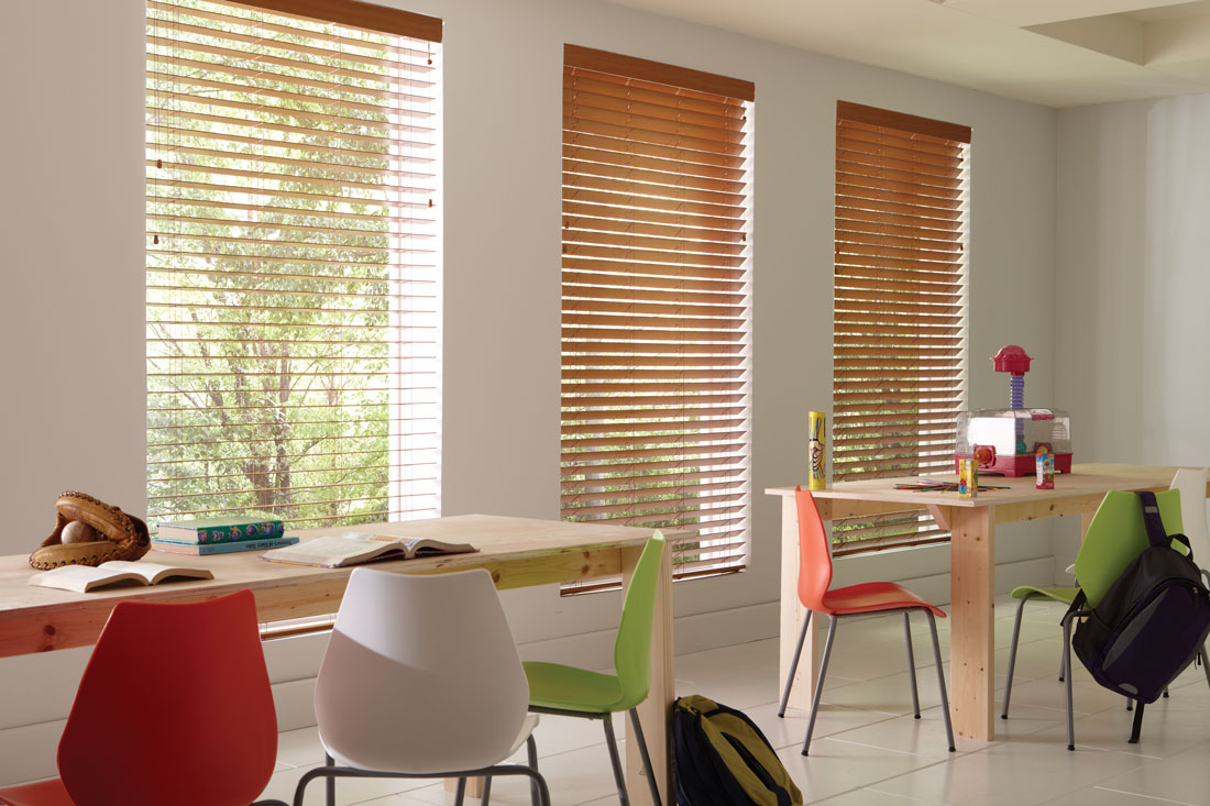 light brown Wonderwood® Wood Blinds in a classroom with multiple colorful chairs