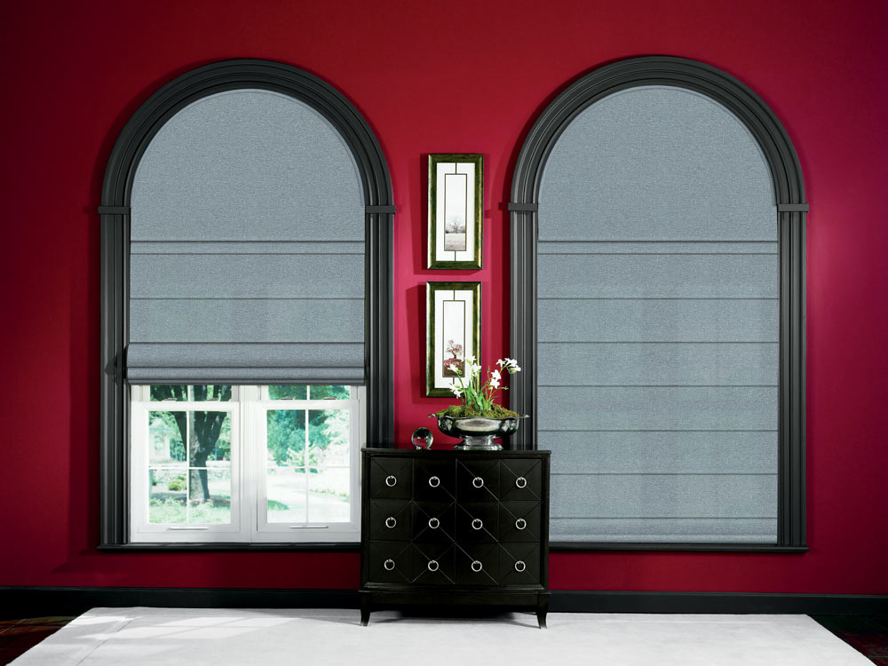 two large gray Genesis® Hobbled Roman Shades half cirlce Custom Shapes above with black window trim and red walls