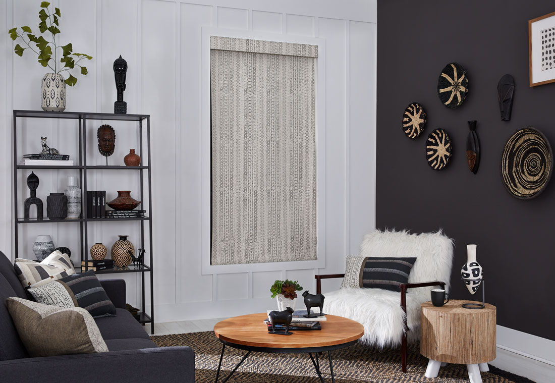 Tan and black patterened Interior Masterpieces® fabric shade with matching fabric cornice in a room with a fluffy chair and couch with accenting custom pillows