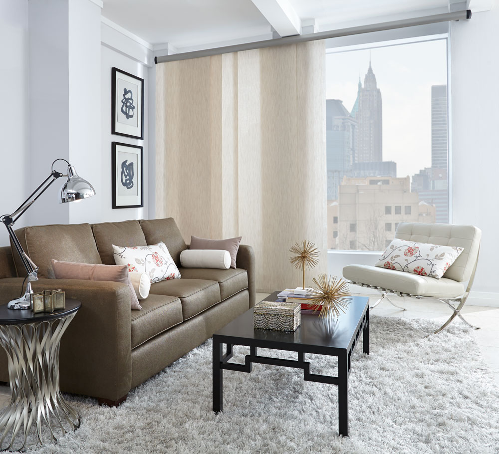 White Genesis® panel track in the open position in a picture window with a view of the city outside and a brown couch with custom Interior Masterpieces® pillows