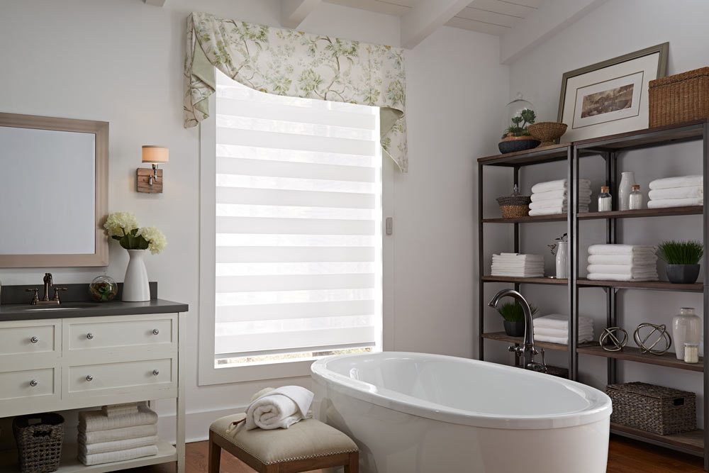 one large white Allure® Transitional Shade with an Interior Masterpeices® green and white floral Fabric Valance in a bathroom behind a stand alone tub and dark shelving