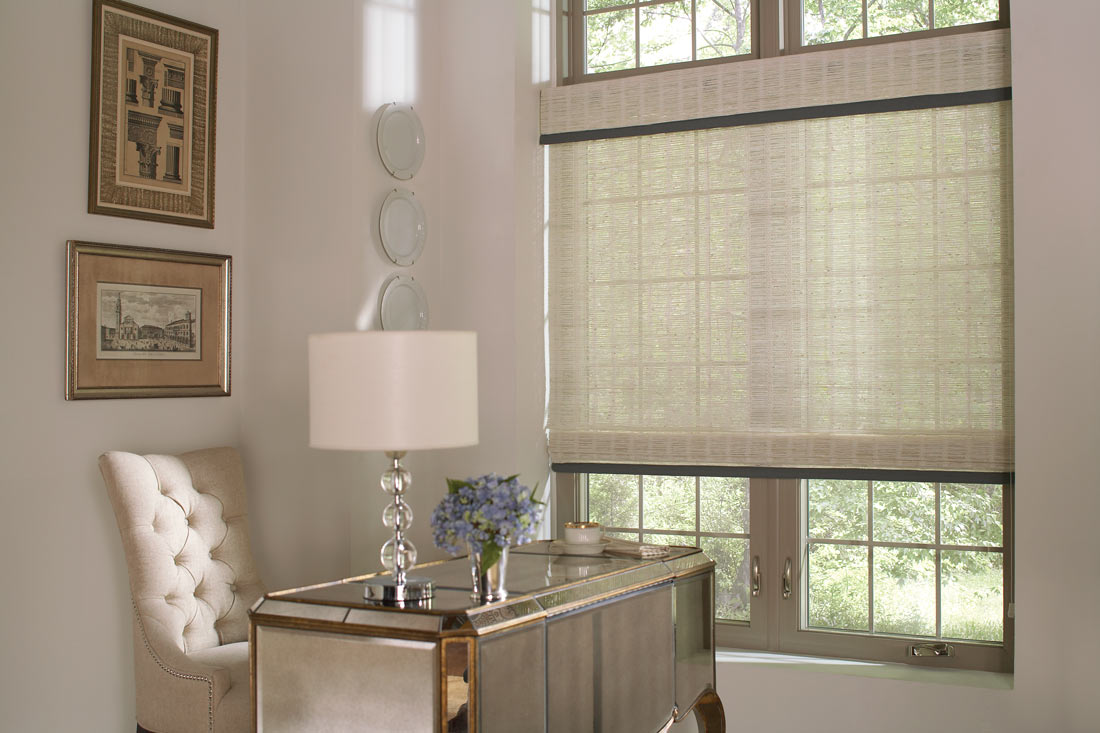 White Manh Truc® Woven Wood Shades with blue Custom Banding behing a table with a lamp and a light colored chair in the corner