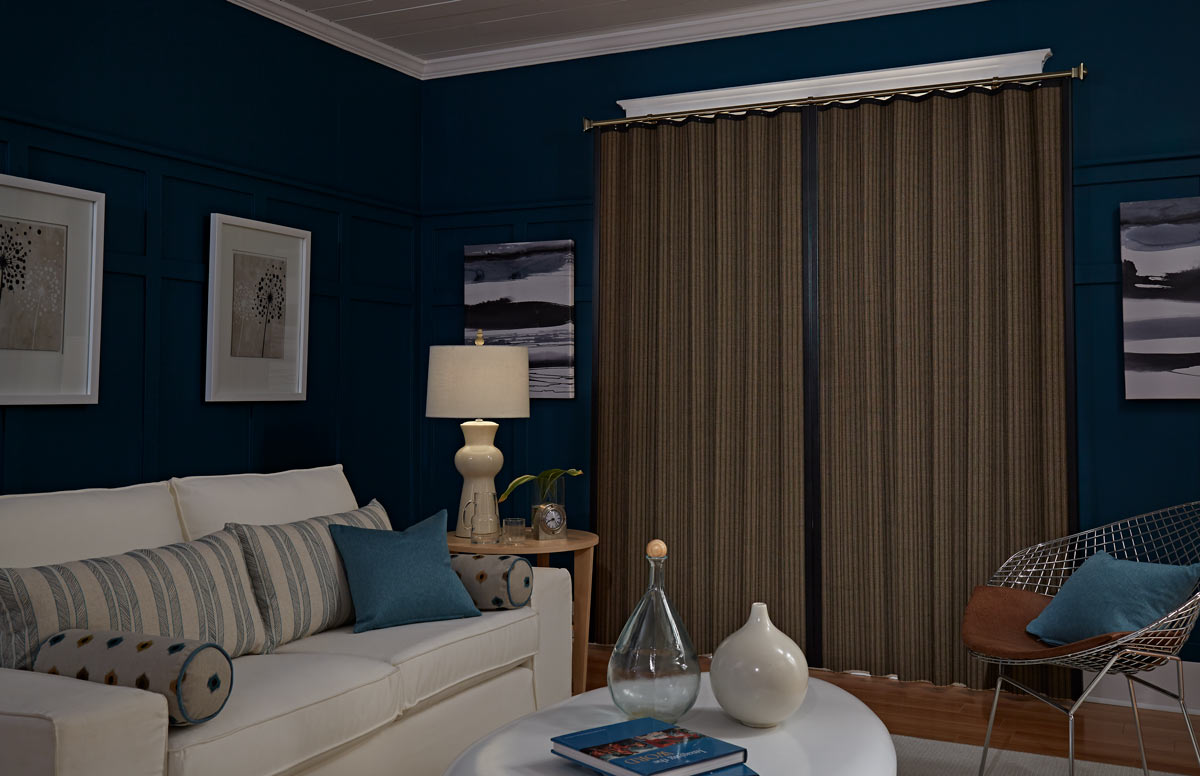 A dark brown Manh Truc® Woven Wood Panel Drape with bronze Custom Hardware against dark blue walls behind a couch with Interior Masterpieces® Custom Pillows
