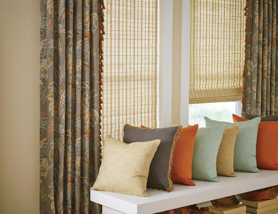 Interior Masterpieces® draperies in a dark color with a floral pattern with Embellishment Trim tassels hanging on the ends of a Manh Truc® woven wood shade with several colorful Interior Masterpieces® custom pillows sitting in front