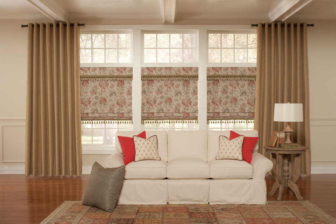 Three tan floral Interior Masterpieces® fabric shades with Embellishment Trim tassles flanked by large tan draperies behind a couch with accenting custom pillows