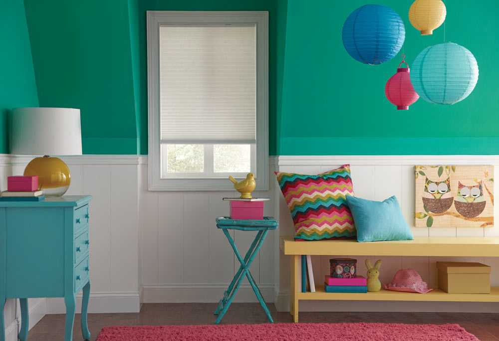 white Parasol® Cellular Shade against a turquoise and white wall with matching Interior Masterpieces® custom pillows on a child's bench with various playthings