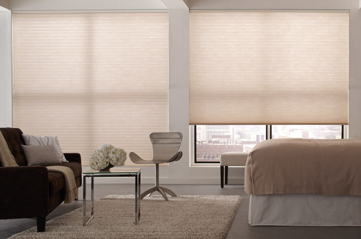 Two large picture windows in a bedroom with a dark sofa and tan bed with Parasol® Cellular Shades behind in a tan fabric